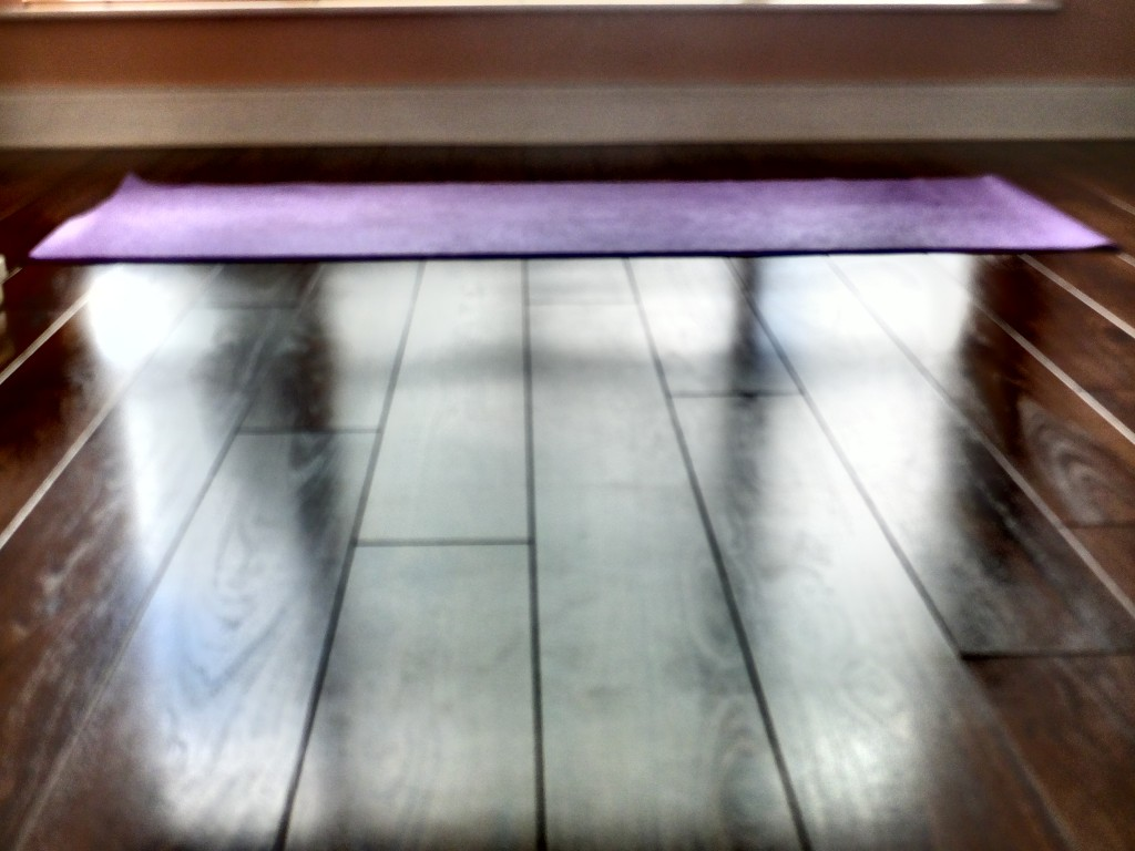 A purple Yoga mat, on a dark brown wooden floor, with daylight creating moody shadows.