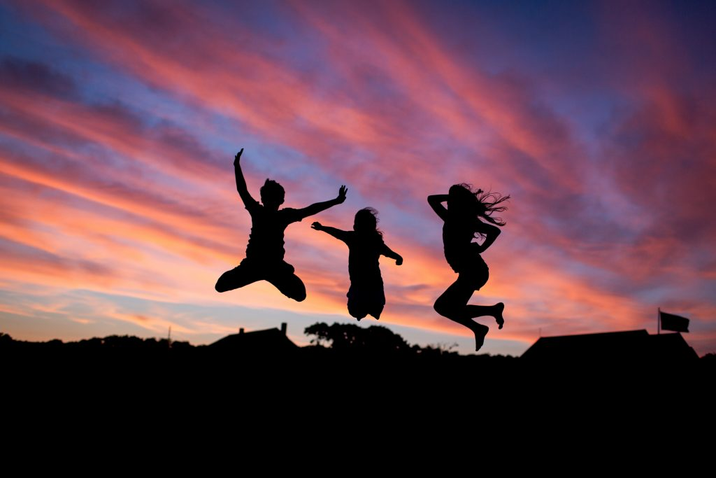 Three children, with a sunset behind them, jumping in the air with fun and Yoga in their hearts.