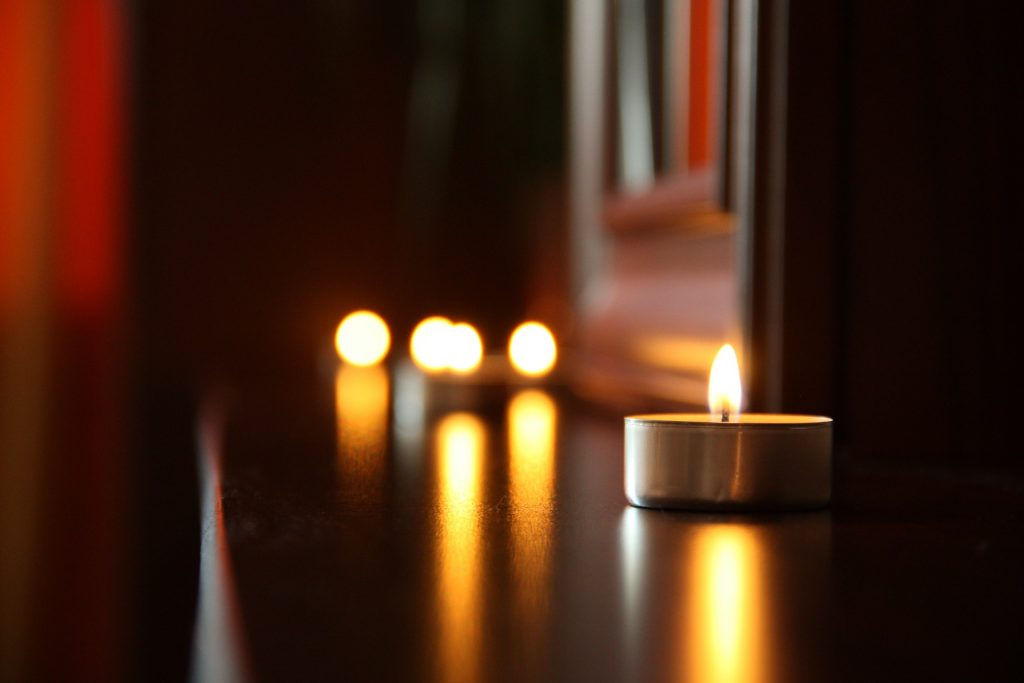 A shelf with small votive candles lighting to create a quiet ambience in the room.